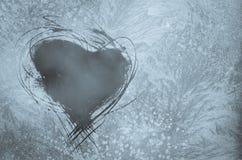 Verkratztes Herz auf eisigem Fenster Stockbild
