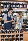 Verkäufer Showing Wine Bottle zum Kunden Stockbild