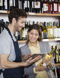 Verkäufer Showing Wine Information zum Kunden auf Digital-Tablet Stockfoto