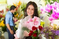 Verkäuferin und Abnehmer im Blumenladen Stockfotos