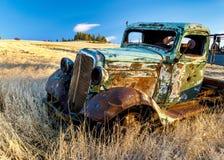 Roestige oude vrachtwagen op een landbouwbedrijfgebied stock afbeelding