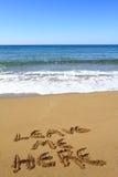 Verlaat me hier, geschreven op strand Stock Foto