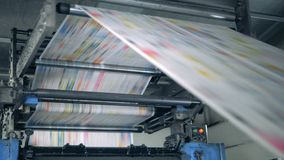 Verlageinheit mit dem Papier, das durch die Maschine rollt Druckzeitungen in der Typografie stock footage