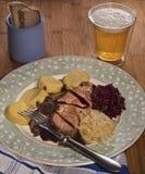 Verlangsamen Sie gebratenen Schweinefleischhals mit den roten und weißen Sauerkraut- und Kartoffelmehlklößen stockfotografie
