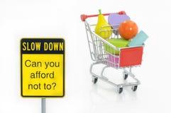 VerlangsamungVerkehrszeichen und Einkaufswagen Stockfoto