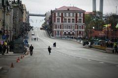 ?verlappade gator av Vladivostok Folket promenerar de centrala gatorna av Vladivostok och den guld- bron royaltyfria bilder