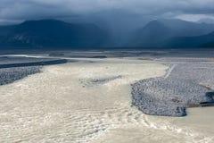 Verlassen Sie Landschaft mit Fluss, Gletscher und stürmischem Himmel, Island Lizenzfreies Stockbild
