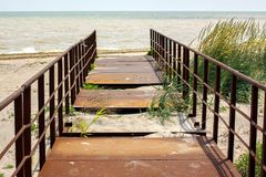 Verlassene alte rostige Brücke, die in das Meer führt Stockfotos