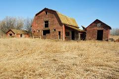 Verlassene alte Scheune und Hallen im trockenen Gras Lizenzfreie Stockfotografie