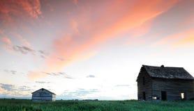 Verlassene Bauernhof- und Holzgebäude am Sonnenuntergang Lizenzfreie Stockfotos