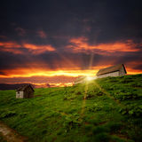 Verlassene Bretterbude auf Hügel und den Sonnenuntergangwolken lizenzfreies stockfoto