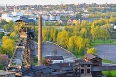 Verlassene Eisengießereifabrik mit einem Bergbauturm und -bäumen und Stadt im Hintergrund Stockfoto