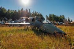 Verlassene gebrochene alte Militärkämpferflugzeuge auf grasartigem Boden Stockbild