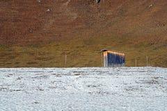 Verlassene hölzerne Halle im schneebedeckten Dorf am Wintertag Lizenzfreie Stockfotos