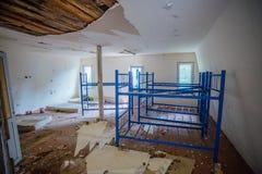 Verlassene Herberge Gruseliges schmutziges und verlassenes Schlafzimmer mit gebrochenen Wänden und Doppeldeckerbett lizenzfreies stockfoto