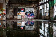 Verlassene Industriegebäudehalle mit Graffiti stockfotografie