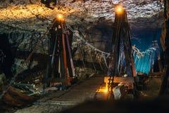 Verlassene Kalksteinuntertagehöhle mit alter Holzbrücke- und Kerzenbeleuchtung Stockbilder