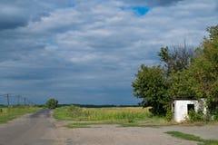 Verlassene Landstra?e durch ein Feld und einen bew?lkten Himmel stockbilder