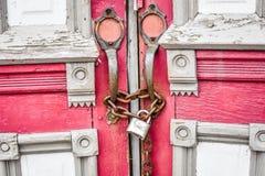 Verlassene rote Kirchen-Türen mit Kette und Verschluss