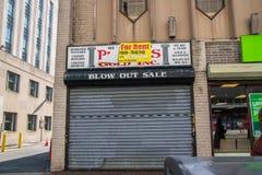 Verlassene Speicherfront des Geschäfts, die Bankrott ging Das Sicherheitstor ist geschlossen stockbild