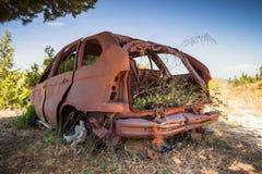 Verlassene verrostete Fahrzeugkarosserie mit wachsendem Gras Lizenzfreie Stockbilder