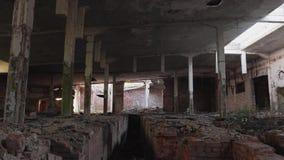 Verlassene zerstörte Fabrik Die Strahlen der Sonne glänzen durch die Löcher in den Wänden stock footage