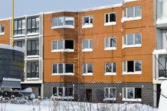 Verlassener Bau eines mehrstöckigen Gebäudes Turmkran und ein Haus mit defektem Glas Winter Russland Stockfotos