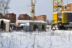 Verlassener Bau eines mehrstöckigen Gebäudes Turmkran und ein Haus mit defektem Glas Winter Russland Stockbilder