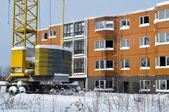 Verlassener Bau eines mehrstöckigen Gebäudes Turmkran und ein Haus mit defektem Glas Winter Russland Lizenzfreies Stockfoto