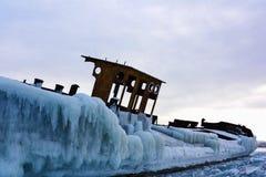 Verlassener gefrorener Lastkahn auf dem Ufer von gefrorenem See stockfotos