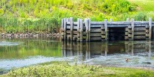Verlassener hölzerner Pier mit Anhäufungen auf einem flachen Fluss Stockfoto