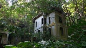 Verlassener Hotelerholungsort überwältigt durch Anlagen im Dschungelwald, Asien Natur gegen Stadt stock video