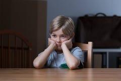Verlassener Junge, der niedergedrückt glaubt Lizenzfreies Stockbild