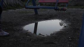 Verlassener Kind-` s Spielplatz, trauriges Kind der Unschuld, das auf einem Schwingen schwingt Reflexion in den Pfützen stock video