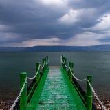 Verlassener Pier in den dunklen bedrohlichen Wolken des Sonnenaufgangs Lizenzfreies Stockfoto