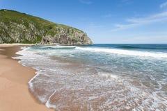 Verlassener sandiger Strand auf dem Hintergrund des blauen Himmels, der Meereswogen und des felsigen Ufers Stockbild