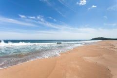Verlassener sandiger Strand auf dem Hintergrund des blauen Himmels und der Meereswogen Stockbilder