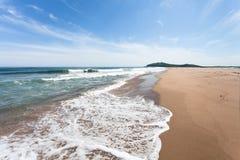 Verlassener sandiger Strand auf dem Hintergrund des blauen Himmels und der Meereswogen Lizenzfreies Stockbild