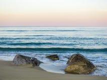 Verlassener sandiger Strand bei Sonnenuntergang Apfelbaum, Sonne, Blumen, Wolken, Wiese? lizenzfreie stockfotos