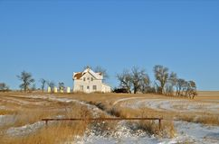 Verlassener Schnee umfasste Grasland-Haus stockbild