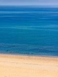 Verlassener Strand mit leuchtendem blauem Meer Lizenzfreies Stockfoto
