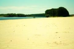 Verlassener Strand mit Paaren Stockfotografie