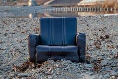 Verlassener Stuhl durch den Fluss Stockfotografie