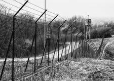 Verlassener Wachkastenturm lokalisiert durch ein Netz mit Stacheldraht Stockbilder