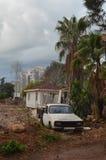 Verlassenes altes Auto nahe altem Haus mit Palmen Stockfoto