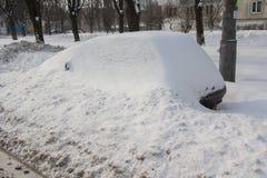 Verlassenes Auto geholt durch Schnee auf einem Straßenrand lizenzfreies stockfoto