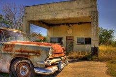 Verlassenes Auto geparkt an verlassener Tankstelle Stockbild