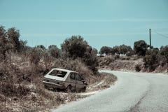 Verlassenes Auto und einsame Straße Stockfoto