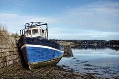 Verlassenes Fischerboot am Dock bei Ebbe Stockfotografie