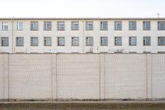 Verlassenes Gebäude umgeben durch große weiße Backsteinmauer lizenzfreies stockbild
